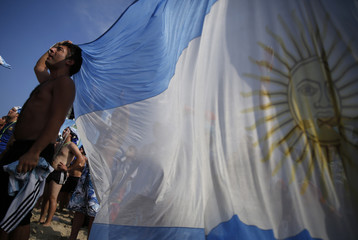 An Argentinian soccer fan holds national flag as he watches 2014 World Cup between Argentina and Switzerland at Copacabana beach in Rio de Janeiro
