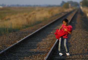 A migrant child holds a baby as she arrives at a collection point near the Serbian-Hungarian border in Roszke