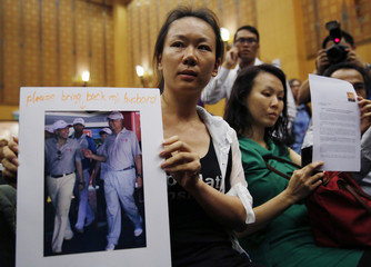 The wife of a passenger aboard the missing Malaysia Airlines Flight MH370, holds a picture of her husband walking with Malaysia's Prime Minister Razak, at a news conference in Putrajaya
