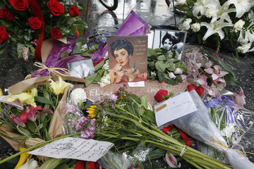 Flowers, photographs and notes from fans adorn the Hollywood Walk of Fame star of actress Elizabeth Taylor in Hollywood,California