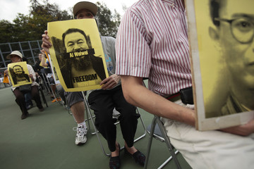 Pro-democracy protesters hold photos of detained Chinese artist Ai Weiwei during a protest in Hong Kong