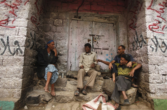 People chat as they sit next to a closed shop in the Old City of Ibb, the provincial capital of Yemen's central province of Ibb
