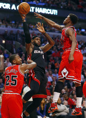 Miami Heat's James passes over Chicago Bulls' Teague and Butler during their NBA basketball game in Chicago