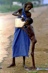 A starving Somali child is given water in Baidoa