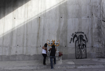 Two women pray at an altar of La Santa Muerte (The Saint of Death) and next to a graffiti of the saint at a highway in Tierras Prietas