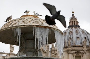 Ice covers a frozen fountain as Pope Francis leads his Sunday Angelus prayer in Saint Peter's square at the Vatican