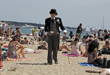A man dressed as Charlie Chaplin walks on the beach in Cannes during the 65th Cannes Film Festival