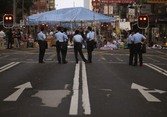 Policemen stand guard on a main road where pro-democracy protesters set up tents during a blockage at Hong Kong's Mongkok shopping district