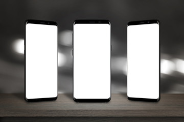 Three mobile phones with isolated screen for mockup on the table. Bokeh lights in background.