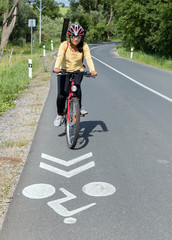Young woman cyclist ride on bike at the road with signpost for bicyclist