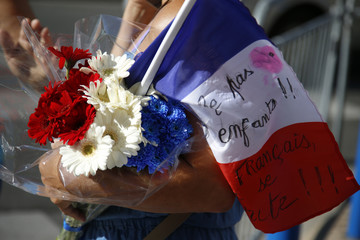 A woman carries blue, white and red flowers and a French flag as a tribute to victicms two days after an attack by the driver of a heavy truck who ran into a crowd on Bastille Day killing scores and injuring as many on the Promenade des Anglais, in Nice