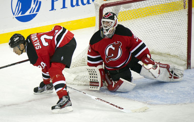 New Jersey Devils Bryce Salvador passes stick to Martin Brodeur after he lost it while playing Ottawa Senators in NHL game in Newark