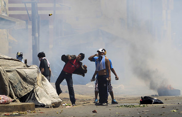 Workers and residents living close to the La Parada wholesale market throw objects during clashes with riot police officers in Lima