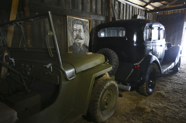 Portrait of Soviet dictator Stalin is seen behind cars from collection of Tsitovich, who finds and restores old cars and motorcycles, at his base in Zabroddzie