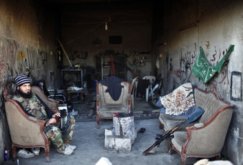 A Free Syrian Army fighter sits in a garage used as a gathering place for the rebels near the front line in Aleppo