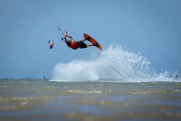 Kite sportsman jumping with splash of water, crystal sea, kiteboarding water sports, active life style. Kiteboarding and kitesurfing water sports, recreational hobby and fun. Sea, beach and clear sky