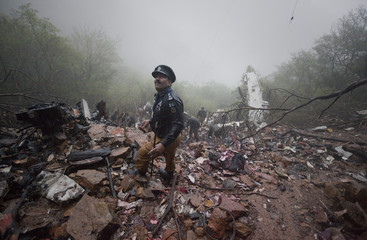 A policeman looks towards the wreckage of an Airblue plane at the crash site during a heavy downpour in Islamabad's Margalla Hills