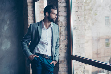 Success concept. Stylish young bearded man is standing near the window and looking far. He is in a suit and, with hands in pockets, pensive and concentrated