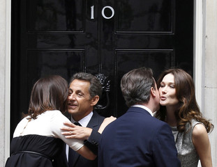 Britain's Prime Minister Cameron, and his wife Samantha, say goodbye to French President Sarkozy, and his wife Carla Bruni-Sarkozy, outside number 10 Downing Street in London