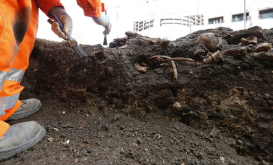 An archaeologist works near skeletons found in the Bedlam burial ground on the future site of a Crossrail ticket hall next to Liverpool Street Station in London