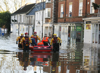 Members of the emergency services rescue a group of people from a flooded street in Tadcaster, northern England