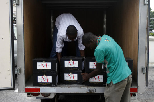 Men unload champagne from a truck at a hotel in Lagos