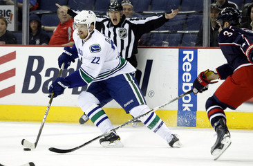 Vancouver Canucks' Daniel Sedin fights for the puck with Columbus Blue Jackets' Marc Methot during the first period of their NHL hockey game in Columbus