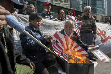 Rising Sun flag with a picture of Japanese Prime Minister Abe and Tojo, is burnt during protest outside the Japanese Consulate in Hong Kong