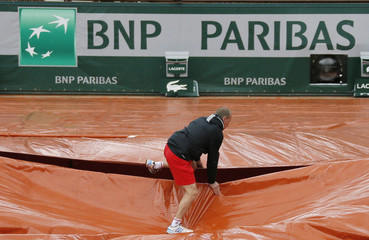 A grounds crew member covers the clay court from rain near the logo of BNP Paribas during the French Open tennis tournament at Roland Garros in Paris