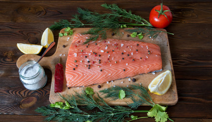 Fresh salmon fillet with lemon, salt, tomato, herbs on wooden background. Close up. Top view. Concept of healthy diet.