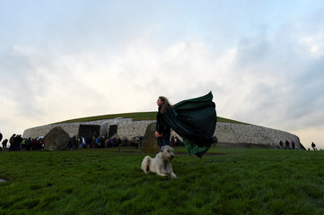 Rebecca Smith poses for a photograph at the winter solstice with her Irish Wolfhound dog called Amazing Grace at the 5000 year old stone age tomb of Newgrange in the Boyne Valley at sunrise in Newgrange