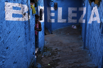 """A woman looks on outside her house next to the word """"Beautiful"""" in an alley (viela), in the Brasilandia favela of Sao Paulo"""