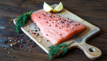 Fresh salmon fillet with aromatic herbs, spices on cutting board on wooden background. Top view. Closeup.