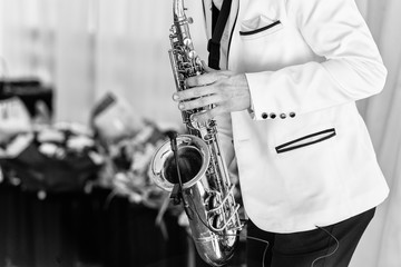 Saxophonist in white jacket plays the saxophone. Saxophonist jazz man with saxophone on wedding party