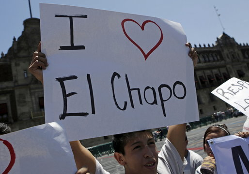 """A man holds up a poster supporting drug lord Joaquin """"El Chapo"""" Guzman, that reads: """"I Love El Chapo"""" outside Palacio Nacional in Zocalo Square, downtown Mexico City"""