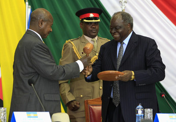 Kenya's President Kibaki hands over gavel, symbol for authority of chair, to Ugandan counterpart Museveni during closing ceremony of the 14th Summit of East African Community heads of state in Nairobi