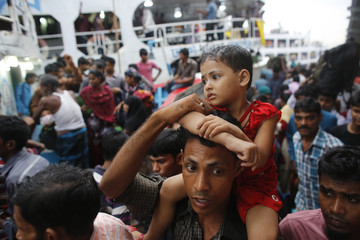A father boards on an overcrowded passenger boat with his child sat on his shoulders at Sadarghat boat terminal in Dhaka
