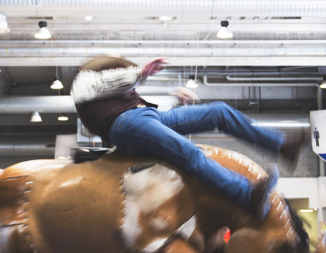 Cowbow participant riding a crazy mechanical bull