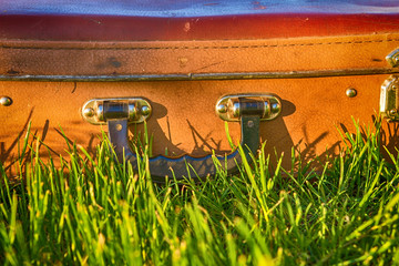 Vintage antique suitcase, pen and lock close-up on a background of green grass travel concept