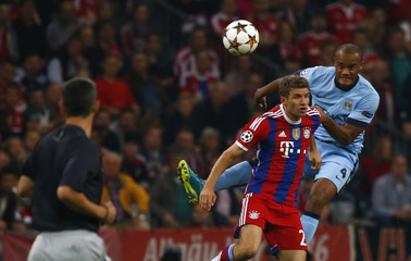 Bayern Munich's Mueller jumps for header with Manchester City's Kompany during Champions League soccer match in Munich