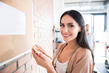 Cheerful smiling lady keeping notes