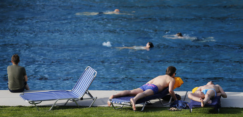 People relax at a public swimming pool on a sunny day in Vienna