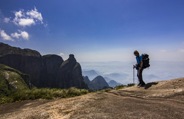 man with backpack standing on top of mountain with blue sky with clouds