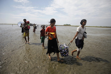 People displaced by recent violence in the Kyukphyu township carry their belongings as they arrive by boats to Thaechaung refugee camp
