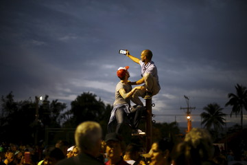 Fans take photographs while sitting on a pole before a free outdoor concert by the Rolling Stones at the Ciudad Deportiva de la Habana sports complex in Havana