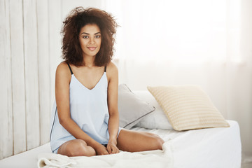 Beautiful african girl in sleepwear sitting on bed at home smiling looking at camera.