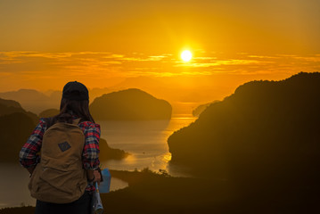 Traveler women with map travel see the mountain veiw in the sunrise