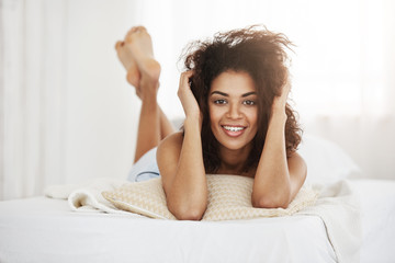 Beautiful happy african girl lying on bed at home smiling looking at camera.