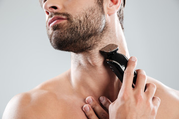 Cropped image of a bearded man using electric razor