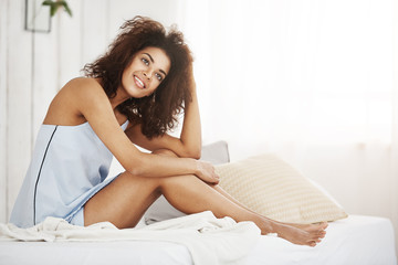 Dreamy tender african girl in sleepwear sitting on bed in morning smiling thinking. Copy space.